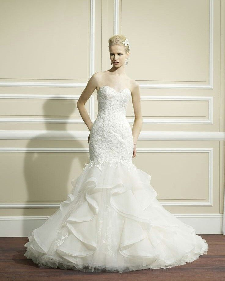 Trending This Moonlight Couture fit and flare bridal gown has gorgeous lace appliques throughout the bodice and an organza ruffle skirt with a chapel train that