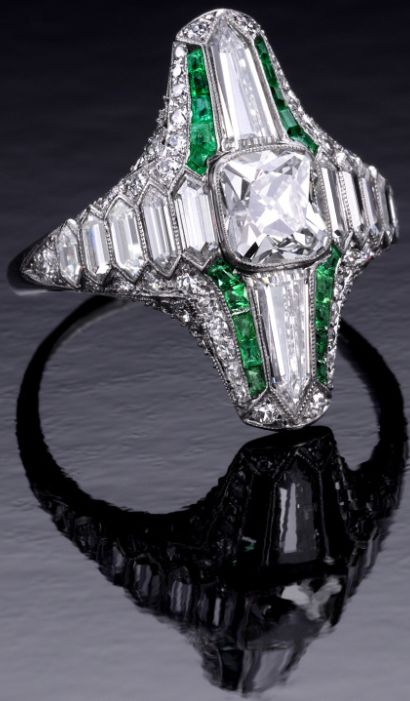 Unusual Art Deco diamond and emerald ring, c. 1920. Via @1stdibs. This rare piece contains many unusual diamond cuts accented with calibre emeralds and small round diamonds: a swiss cut diamond weighing 1.68 cts flanked east and west by 5 graduated double bullet-cut diamonds and north and south by a tapered bullet-cut diamonds.