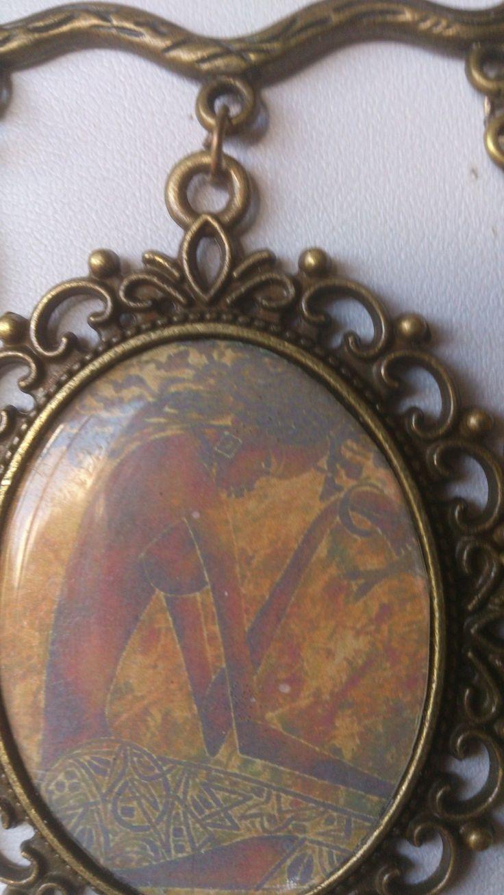"""http://www.alittlemarket.com/boutique/gaby_feerie-132444.html COMMENTAIRES DE GABY FEERIE CREATEUR de BIJOUX en MODELE UNIQUE : broche ethnique femme africaine Vénus noire en fondu de couleur orange et marron """"Afrique adieu"""" -  portrait voilé comme les premiers tirages photos avec pendentif fleur d'arum et fleurs exotiques couleur bronze"""