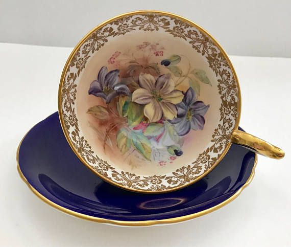 Vintage Aynsley china tea cup and saucer, made in England. A stunning cabinet duo, cobalt blue ground with gold gilding outside, inside a hand painted flowers, signed G. Bentley. It is in good condition, no chips, cracks or crazing and both pieces ring nicely. Please Note: The