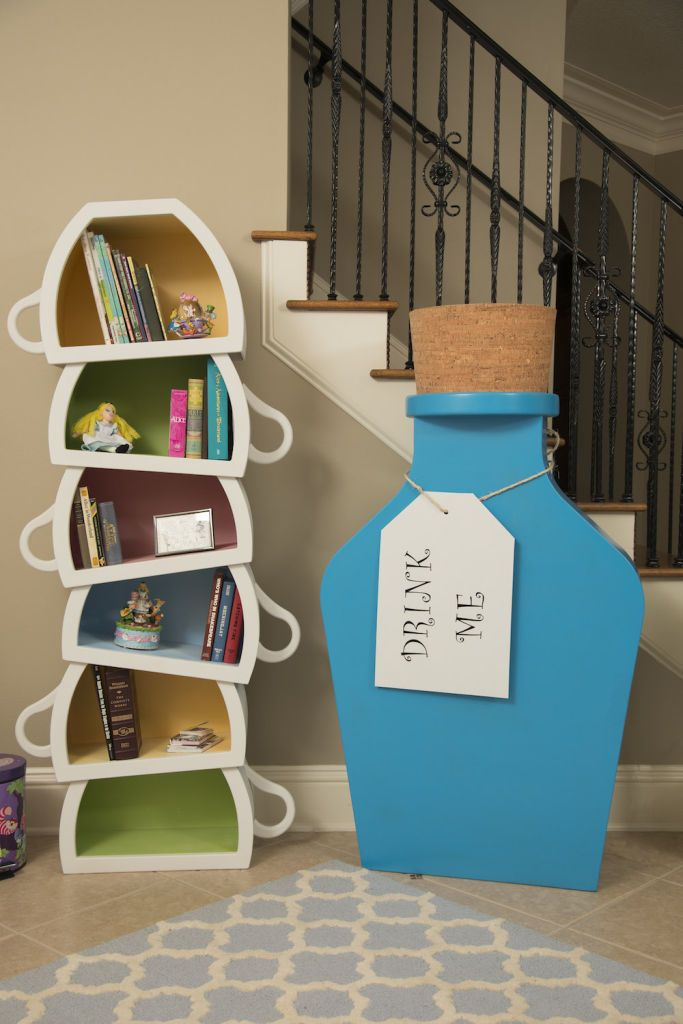This teacup bookshelf and larger-than-life Drink Me statue are straight out of Wonderland. | Ashley Eckstein Alice in Wonderland Dining Room Tour