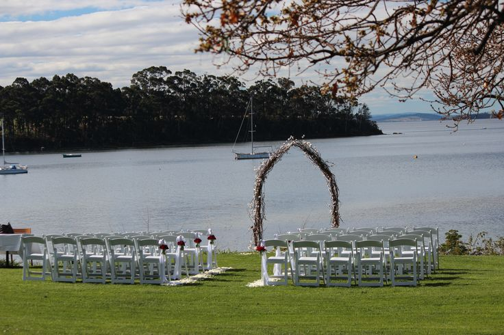 Peppermint Bay wedding ceremony with rustic twig arch, white folding chairs and rose petals