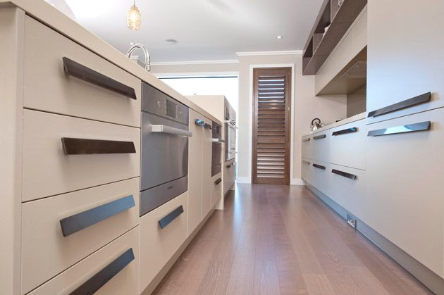 Modern and spacious, the stainless steel oven and slimline door handles make this kitchen very chic. The clever use of wood brings warmth to this kitchen, avoiding a clinical look. #ClassicBuilders #KitchenDesign