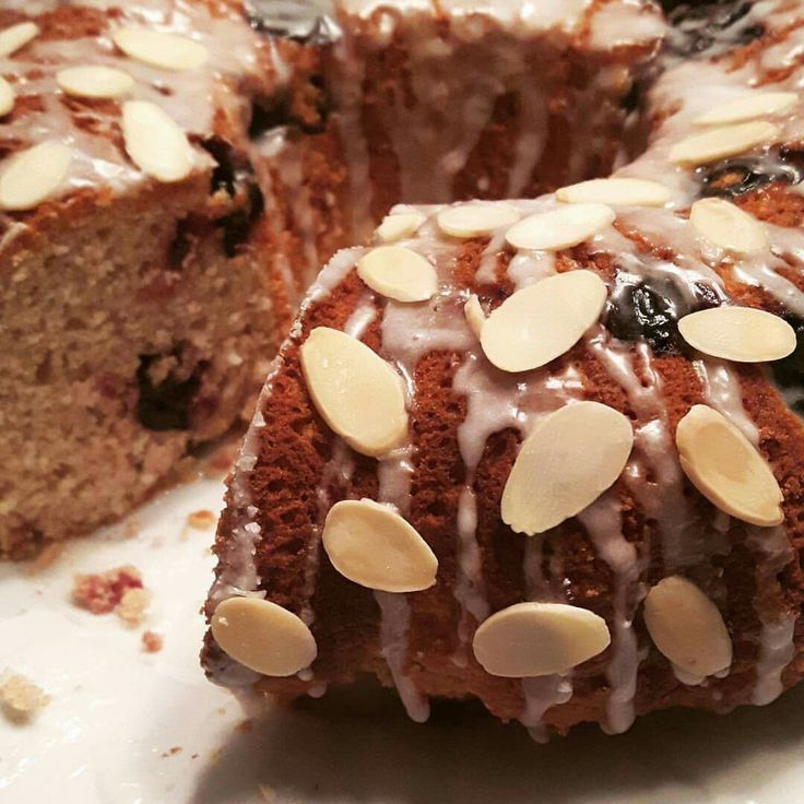 Coconut and dark cherry coffee cake. Light in tge sweetness and warmed with cinnamon. Finished with a simple white glaze and toasted almonds.