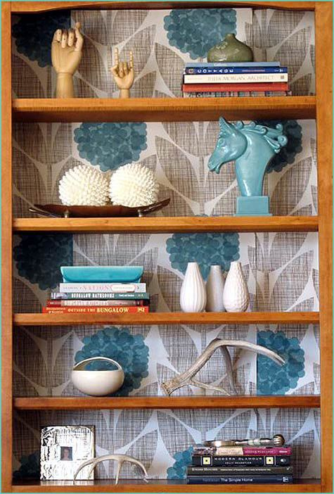 Photo inspiration showing an oak bookcase with a wallpapered background added.  What I love about this picture is that the color in the wallpaper is complimentary to the orange tone of oak and they also incorporated some items of that color on the shelves.