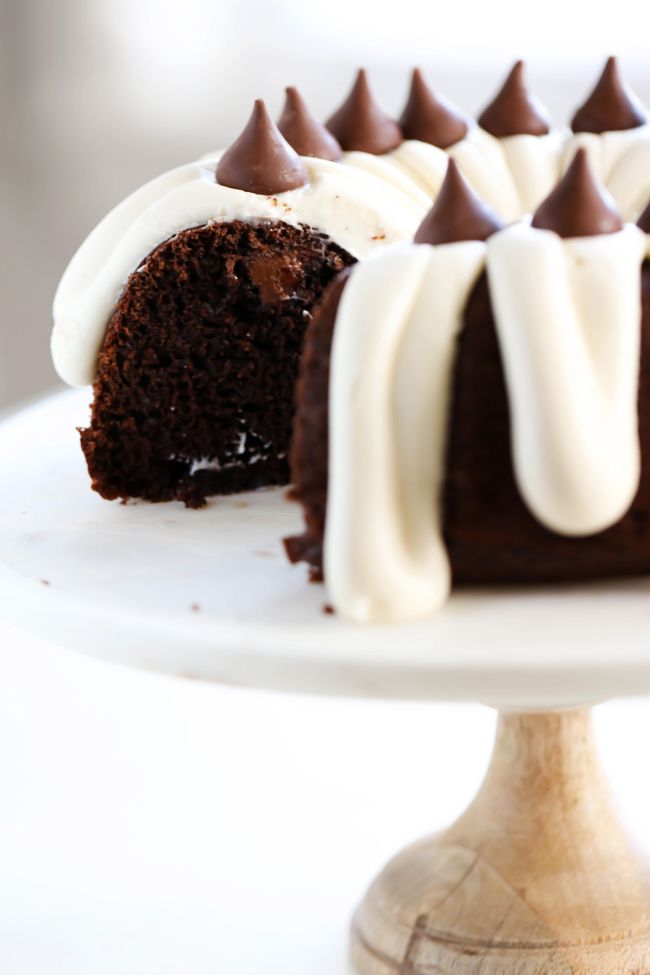 This HERSHEY'S KISSES Bundt Cake is an extremely moist cake loaded with KISSES Chocolates inside. It is finished off with a thick cream cheese frosting which compliments the flavor perfectly! #sponsored HERSHEY'S Chocolate