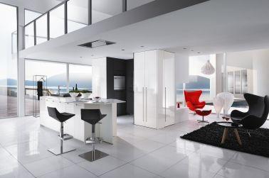 Si vous souhaitez une cuisine ouverte, le blanc reste le meilleur choix pour l'intégrer au reste de la maison. Le four, le réfrigérateur, et le lave-vaisselle sont encastrés dans une niche couleur carbone. Le reste de la cuisine blanche se marie à la perfection avec l'aménagement du salon grâce à ses lignes épurées