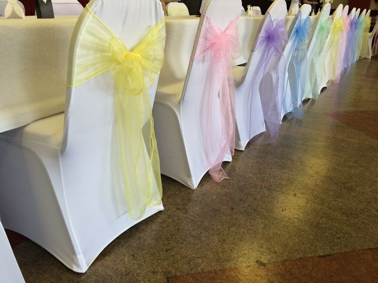 White chair covers with pastel multicoloured organza sashes at a Welsh wedding reception dressed by affinity event decorators