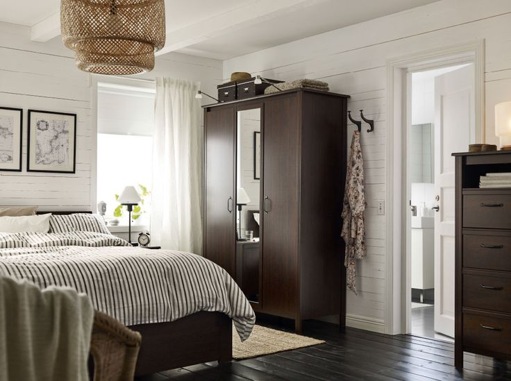 A small bedroom furnished with a wardrobe with two brown doors and one mirror door. Shown together with a brown bed and a chest of drawers.