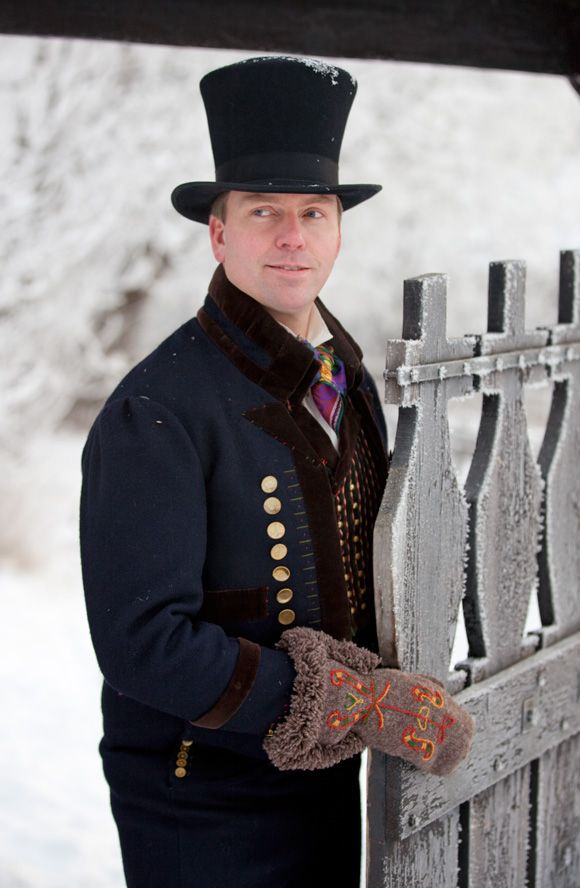 Valdres. This bunad is made of dark blue cloth with brown velvet details. He is keeping his hands warm with beautifully embroidered mittens.