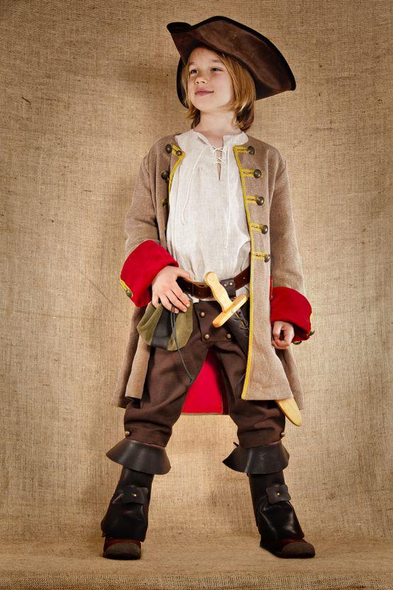 """Ce costume de pirate inspiré du 17ème siècle est composé de 3 pièces : Une chemise en lin, un pantalon en coton et une veste en lin et coton lavé. Elle est doublée et agrémentée de nombreux galons et boutons de métal ouvragés. Les revers des manches et rabat de poches sont en velours lisse. Ce costume de fabrication artisanale est disponible du 4 au 12ans à partir de 224€. Tous les accessoires en cuir et en bois sont également disponibles sur le site de """"7 et une Lieues"""""""