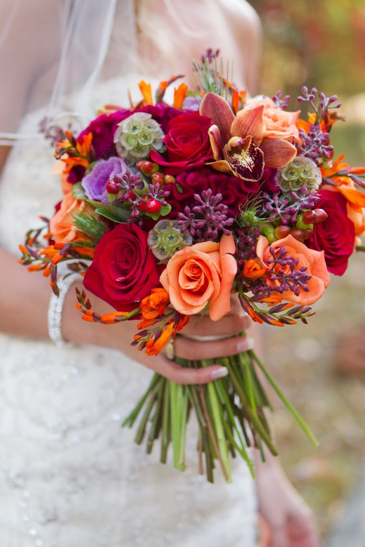 Fall/Autumn Wedding Bouquet: Red Roses, Orange Roses, Orange Cymbidium Orchids, Orange Freesia, Purple Kale, Purple Eucalyptus Seeds, Fuchsia Coxcomb (Celosia), Scabiosa Pods, Red Hypericum Berries, Greenery