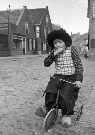 Portret van een kind in klederdracht op een driewieler in de Spuistraat te Spakenburg (gemeente Bunschoten), uit het zuiden. 1945-1950 FF van der Werf (fotograaf)