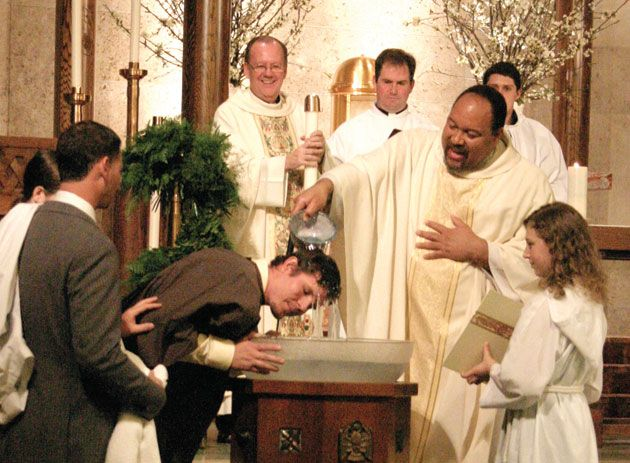 Paulist Fr. Steven Bell baptizing during an Easter Vigil Mass at St. Austin Church in Austin, Texas.  Paulist Fr. John Hurley is at center holding the Easter Candle.  Next to him is then-seminarian Tom Gibbons, CSP.