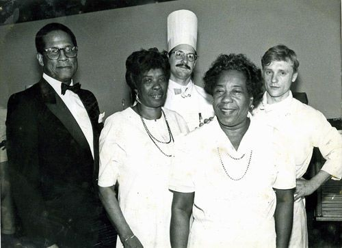 """The Grandmothers of Low-country Cuisine,"" Lucille Grant and Anna Pinckney, partners in a catering business,  Made From Scratch, took charge of a Spoleto fundraising dinner in New York City in 1990 in the aftermath of Hurricane Hugo. They flew up on a private plane carrying 300 lbs. of shrimp, 70 lbs. of crabmeat, 10 lbs. of crab roe, 70 jars of artichoke relish, 3,000 benne wafers and 1,200 cheese biscuits. 700 people attended. [Pictured with chefs Dana Sinkler Jr. and Alexander…"