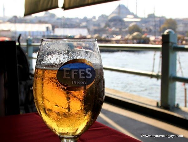 Having an Efes beer while sitting under the Galata Bridge in #Istanbul.