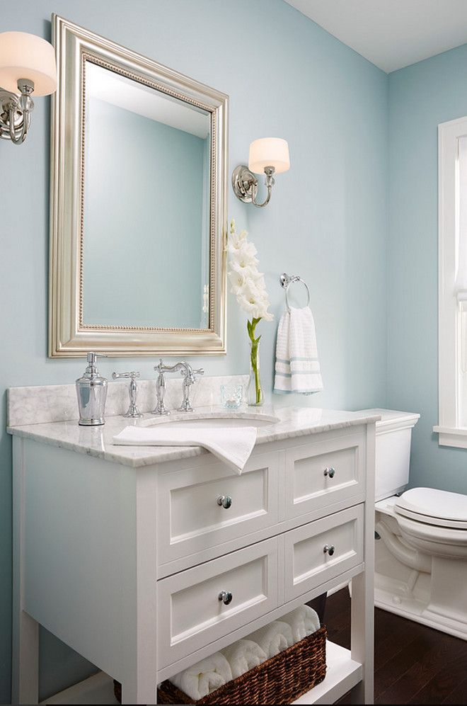 Cape Cod Cottage Remodel. Love that champagne gold oversize mirror in this powder room! #powderroom #homeremodel
