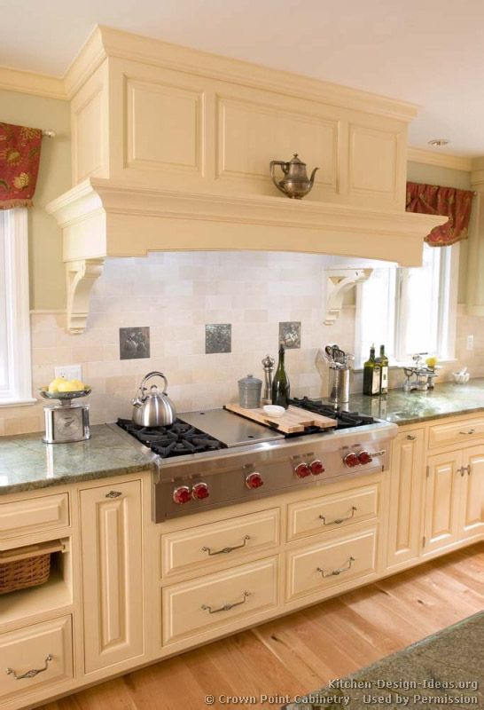 idea of the day traditional antique white kitchen with a large wood range hood over a range top cabinetry and hood by crown point cabinetry