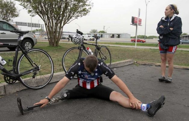 Mike McNaughton stretches before taking part in the Ride 2 Recovery Texas Challenge on Monday, March 28, 2011. McNaughton lost his leg in Afghanistan and had the privilege of jogging with President Bush in 2004. Standing on the right is Claudia Billiot, who recently lost her sister from injuries she sustained while on duty in Iraq.