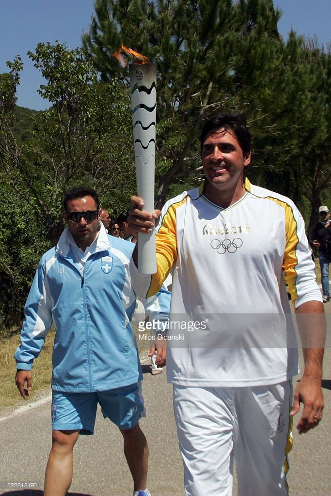 Retired Brazilian volleyball player and coach and second torch bearer Giovane Gavio (R) carries the Olympic torch during the Lighting Ceremony of the Olympic Flame for the Rio Olympic Games on April 21, 2016 in Olympia, Greece. Torchbearers will carry the Olympic Flame from Ancient Olympia on relay through Greece for eight days before a hand-over ceremony at Panathenian Stadium in Athens.   (Photo by Milos Bicanski/Getty Images)