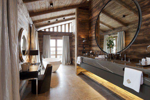 une salle de bain en bois avec un miroir rond et une baignoire design dans un chalet