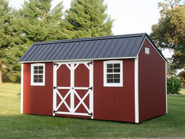 Red painted wooden storage building with a black metal roof