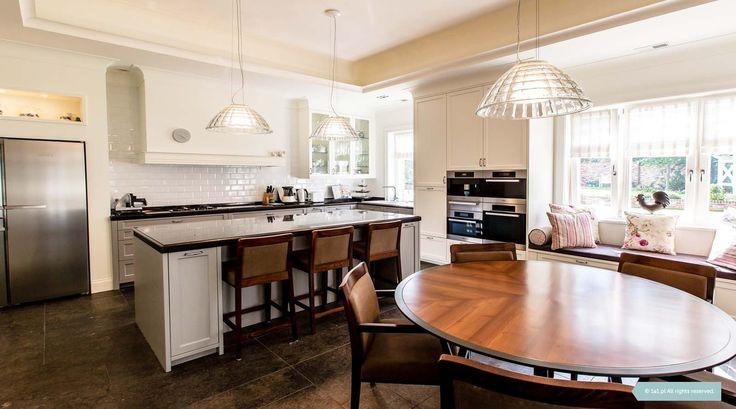 Kuchnia w odcieniach bieli i szarości. Jedyny w swoim rodzaju, duży, okrągły stół jest dopełnieniem tego eleganckiego wnętrza. Projektowanie Wnętrz - Architekt Poznań Kuchnia angielska. Projektant wnętrz. #interior #kitchen  #white