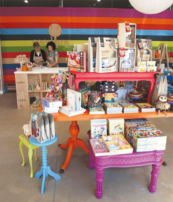 Now HERE'S a swing shop: thrift shop tables repainted in bright enamel colors and arranged to suit whatever merchandise you are featuring. YUM!