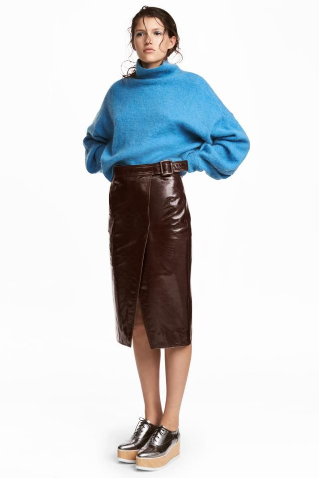 PREMIUM QUALITY. Knee-length wrapover skirt in coated leather with a sewn-in tie belt and buckle at the waist. Flap pockets at the side and a slit at the ba