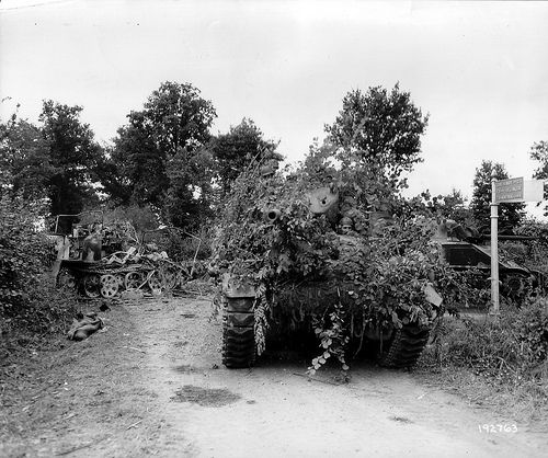 M10 tank destroyer disguised 703-3 battalion 1st Armored Division and the M4 Sherman tank move through the crossroads between Louge-sur-Maire, La Bellangerie and Montreuil-au-Houlme.  In the background a burned-out tractor German SdKfz 7 hours, 88 mm anti-aircraft Cannon Flak18 on the left side of the road lies the corpse of a German soldier.