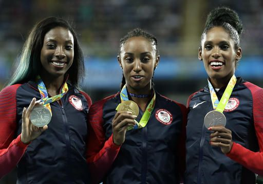 Gold medal winner Brianna Rollins is flanked by silver medal winner Nia Ali, left, and bronze medal winner Kristi Castlin, all from the United States, during the medal ceremony for the women's 100-meter hurdles at the athletics competitions of the 2016 Summer Olympics at the Olympic stadium in Rio de Janeiro, Brazil, Thursday, Aug. 18, 2016. (AP Photo/Dmitri Lovetsky)