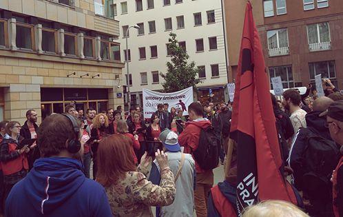 """Zbieramy się i powoli zaczynamy demonstrację MyPrekariat pod Ministerstwem Pracy. Domagamy się stabilnych warunków zatrudnienia, minimalnej płacy godzinowej, obowiązkowych klauzul wymagających zatrudnienia na umowy o pracę przy realizacji zamówień publicznych. Przed demonstracją śpiewa Warszawski Chór Rewolucyjny """"Warszawianka"""""""