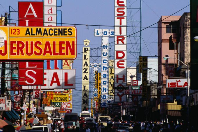 Signs, shops, traffic and people, all on Duarte Avenue, Santo Domingo in the Dominican Republic.