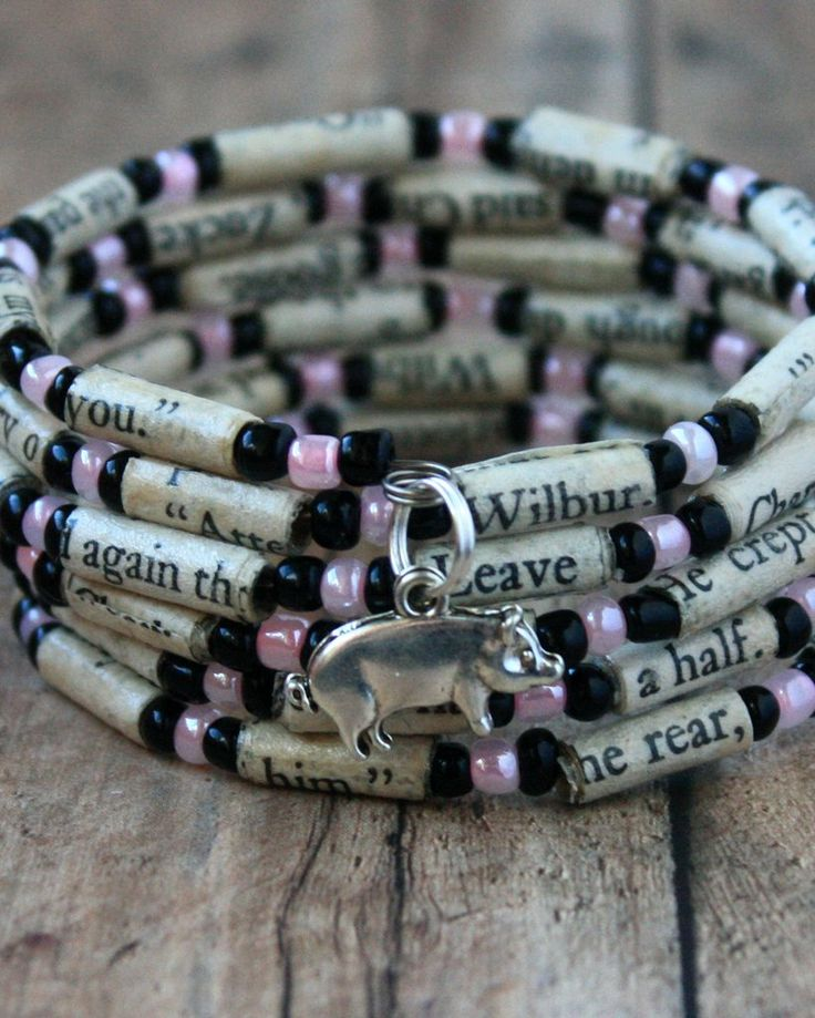 This bright beaded bracelet was made using alternating paper beads and pink and black glass beads. The paper beads were created using pages from the book, Charlotte's Web. The bracelet is completed wi