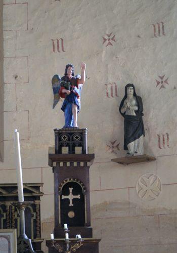 A l'intérieur de l'Eglise d'Arville, des lettres M et des croix de Malte ont été peintes derrière le choeur, sur le mur de l'abside. On retrouve ces deux emblèmes à différents endroits autour du choeur (autel, sculptures sur le mur, ...)