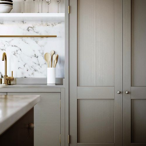 greige/taupe cabinets with marble backsplash + brass faucet