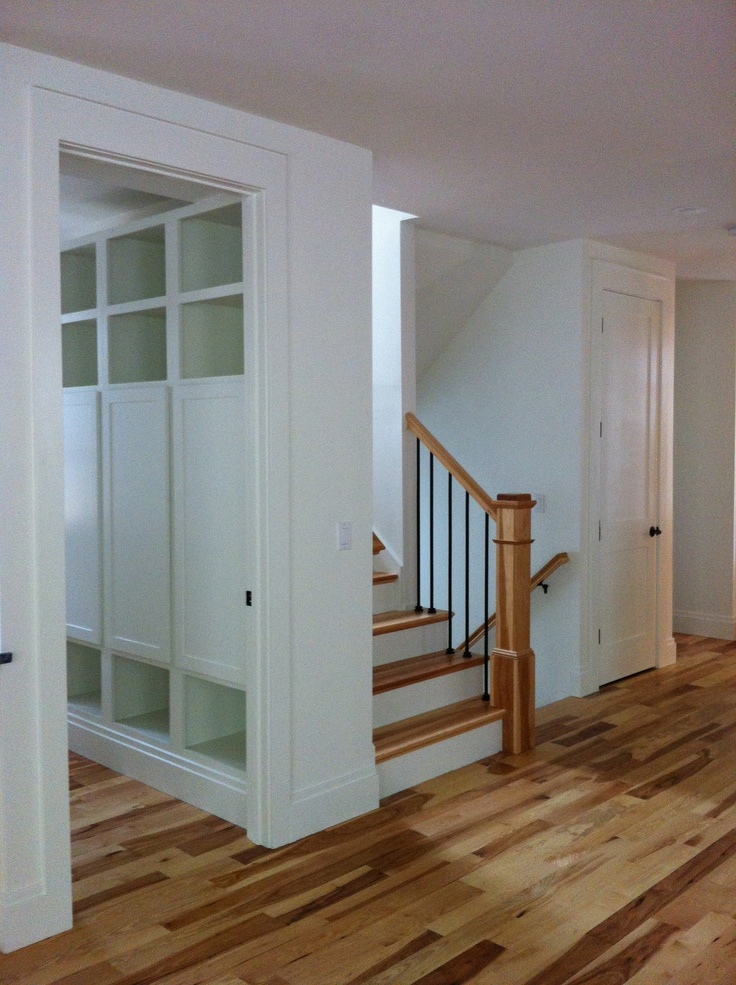natural hickory floors lead to minimalist wooden lockers at mudroom/side entry