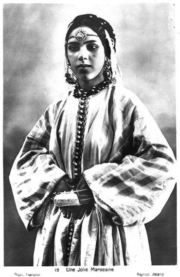 """• Femme marocaine aux bijoux • """"La jeune femme porte des bijoux de fête en harmonie avec le beau caftan en soie à rayures, très en vogue dans les années 1920. Sur le front, un médaillon dit tabâh retenu par un simple cordon en soie tressée, et aux oreilles, une paire de boucles dites dawah en or et pierres précieuses. La ceinture (mdamma) est ganie d'une boucle appelée fekroun."""""""