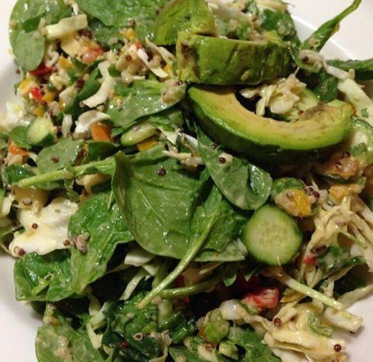 Insalata verde con quinoa, avocado, cetrioli, germogli, spinaci, peperoni e salsa con yogurt di soia