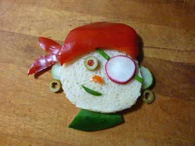 Pirates for Lunch.  All you need for these pirate sandwiches is 2 slices bread, Red pepper (or salami), Olive slices, cucumber, Radish slice (or a slice of red apple), Chives, Orange nose (carrot, orange pepper or cheese), Sandwich filling of choice (turkey, cheese, ham etc.)