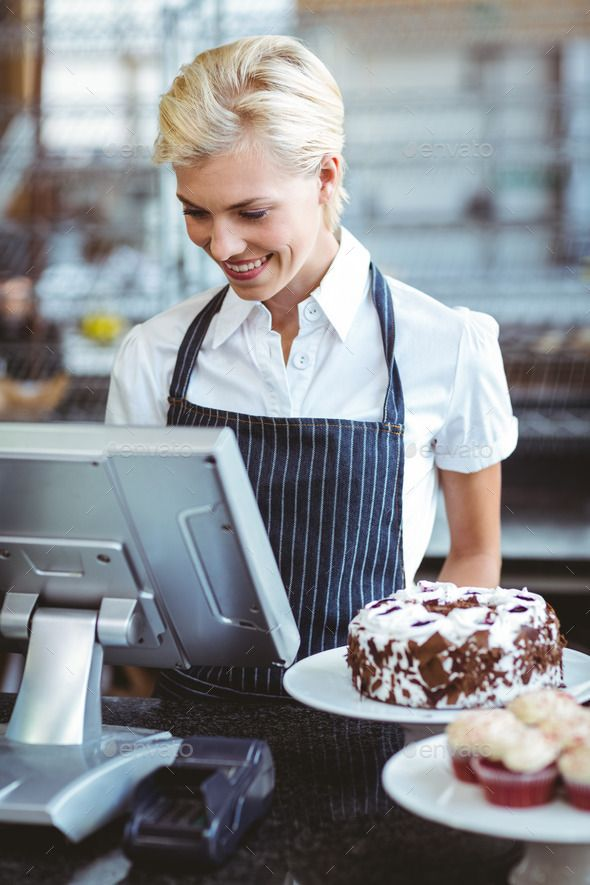 Smiling employee using calculator on counter at the bakery