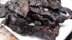 Strips of beef are marinated in teriyaki sauce, soy sauce, and a blend of pineapple and garlic in this easy smoked jerky recipe.