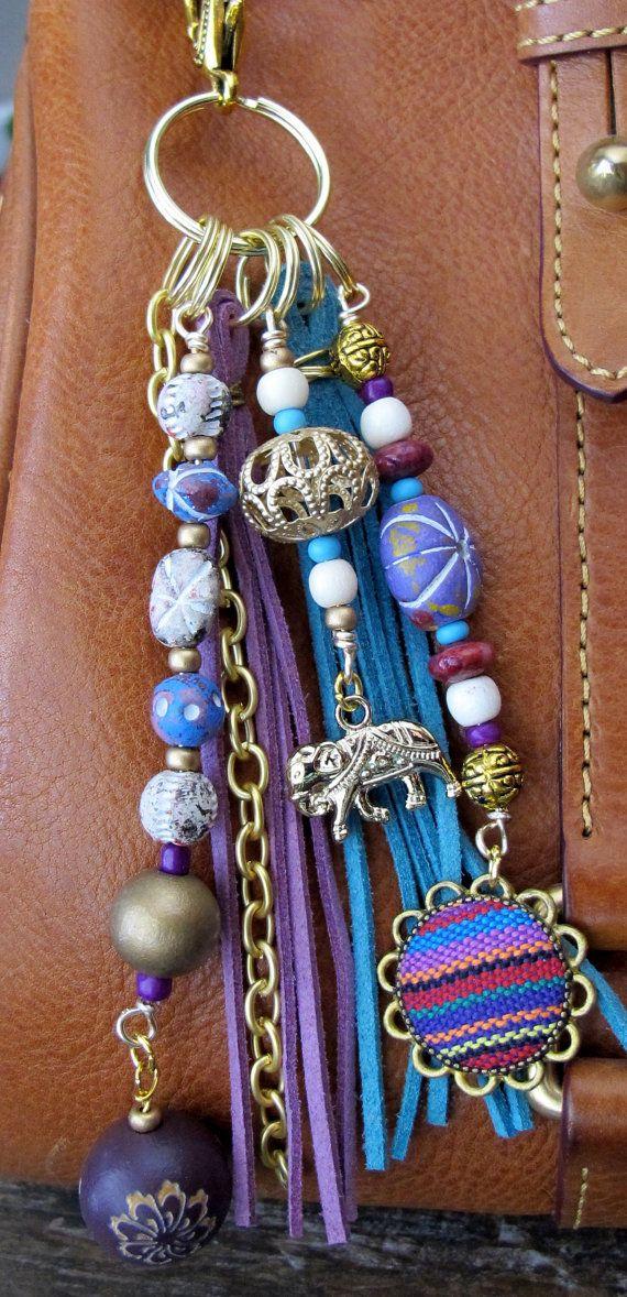 Dieser handgefertigte Quaste Charm einsetzbar wo immer Sie, fügen Sie einige Charme möchten auf Ihre Handtasche, Rucksack, Reißverschluss! Es setzt sich aus einer Messingkette und Anhänger, von denen Stoff/Tapete bedeckt ist, und verschiedene Arten von Perlen - rosa Achat, Holz, Glas und Rocailles. Die Wildleder Quasten sind Lavendel/lila und Türkis in der Farbe blau. Es ist ca. 6,75 lange.
