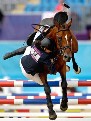 Tamara Vega, of Mexico, falls off her horse Douce de Roulad, during the equestrian show jumping stage of the women's modern pentathlon at the 2012 Summer Olympics, Sunday, Aug. 12, 2012, in London.