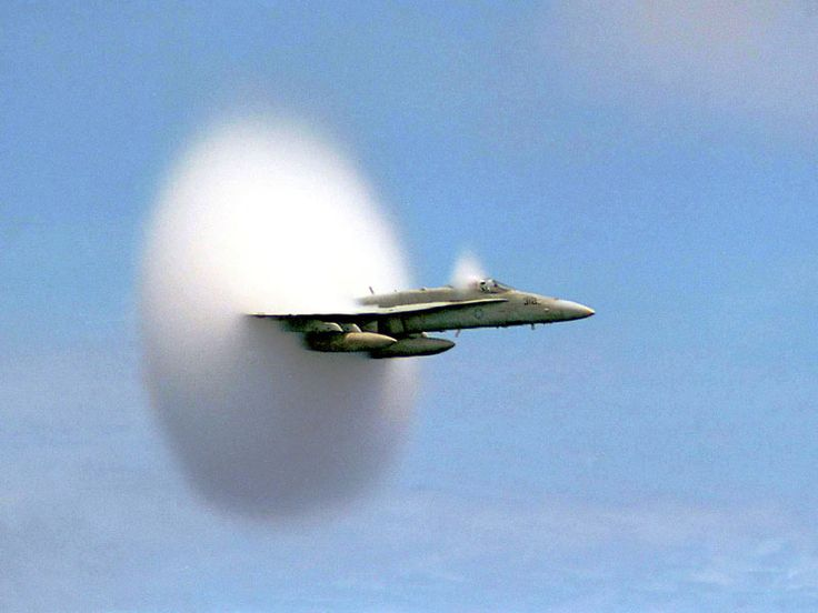 An F/A-18 Hornet was photographed just as it broke the sound barrier. When an airplane travels at a speed faster than sound, density waves of sound emitted by the plane cannot precede the plane, and so accumulate in a cone behind the plane. When this shock wave passes, a listener hears all at once the sound emitted over a longer period: a sonic boom. As a plane accelerates to just break the sound barrier, however, an unusual cloud might form. The origin of this cloud is still debated.