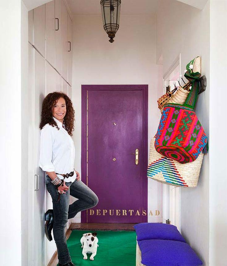 Decoração ousada, porta roxa, tapete verde e acessórios coloridos.