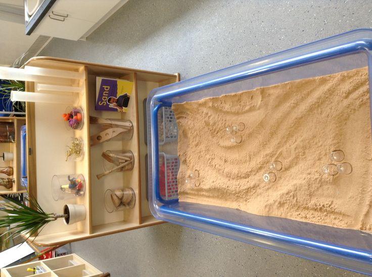 Sand area, using plastic shot glasses for miniature sandcastle building.