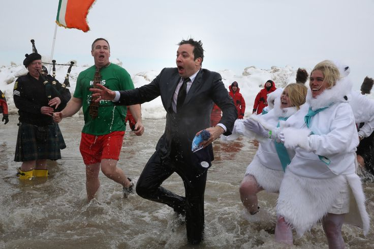 """""""The Tonight Show"""" host Jimmy Fallon walked into Lake Michigan Sunday morning in the promised suit and tie, turned toward the beach, then fall back into the water, going completely under."""