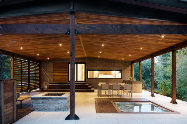 One of the terraces houses an outdoor kitchen, a fireplace, a dining room, a lounge area, and a spa, slightly hidden by cedar shutters and vegetation.