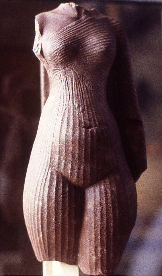 Torso della regina Nefertiti, ca 1345 a.C. Quarzite rossa scolpita a tutto tondo, altezza 29,5 cm. Da Tell el-Amarna. Parigi, Museo del Louvre. Il corpo della regina è rappresentato avvolto da un sottile kalasiris, che lascia nuda la spalla destra raccogliendosi in un nodo sotto il seno. L'abito aderisce al corpo come una seconda pelle, mettendo in evidenza la sinuosità del corpo, la cui prominenza in corrispondenza del ventre richiama con naturalismo anche il concetto della fertilità…